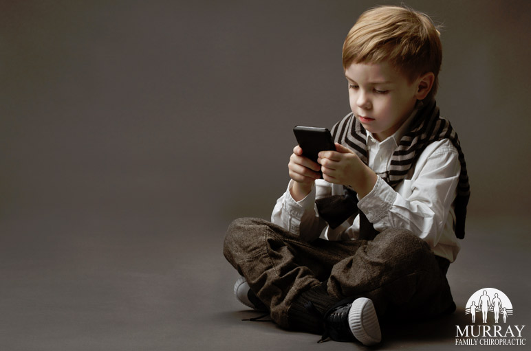 Image of a kid playing on a phone